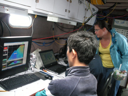 Students watch monitors in the lab aboard a research vessel.