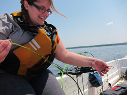 Student examines a strand of eelgrass on Great Bay.