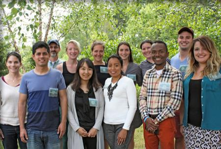 12 new students in a group shot in front of green trees.