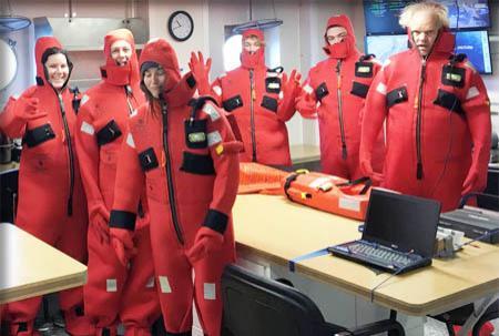 Team poses in red survival suits below deck.