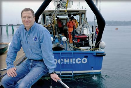 Larry Mayer sits with the stern of the R/V Cocheco behind him.