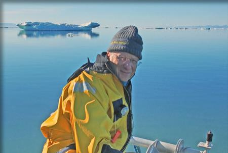 Photo of Larry in sitting in the bow of a small boat in the Petermann Fjord with icebergs in the background.