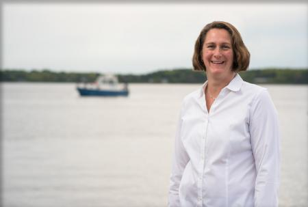 Jen Miksis-Olds stands at the coast with a research vessel sailing in the background.